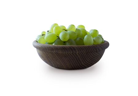 Green grapes Kishmish isolated on white background. Top view. Grapes in a wooden bowl isolated on white background. Vegetarian or healthy eating.Top view.Green grapes Kishmish with copy space for text Imagens
