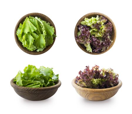 Young lettuce leaves in wooden bowl. Top view. Lettuce isolated on a white background. Green and red lettuce with copy space for text. lettuce leaves isolated on white. Salad from different angles.