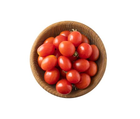 Red tomatoes lay on white background. Top view. Cherry tomatoes on a wooden bowl isolation. Tomatoes isolated on a white background. Tomato with copy space for text. Red tomato isolation on white.