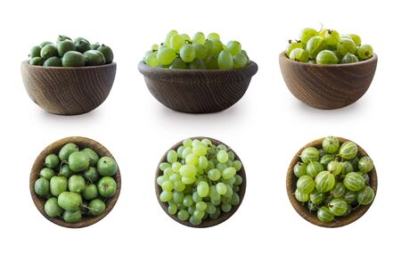 Green fruits isolated on a white background. Collage of different fruits and berries at green color.Green baby kiwi fruit actinidia, gooseberry, green grapes in a wooden bowl. Fruit and berry on white