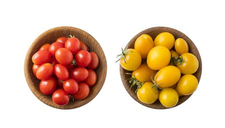 Red and yellow tomatoes lay on white background. Top view. Cherry tomatoes on a wooden bowl isolation. Tomatoes isolated on a white background. Copy space. Set of tomatoes of different varieties.