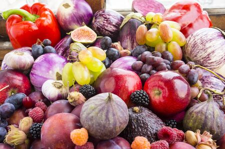 Background of fresh vegetables and fruits. Purple eggplant, plums, figs, apples, raspberries, avocado, grape, hazelnut, sweet pepper, tomato and garlic.Immunity system improvement. Antiviral treatment Stock fotó