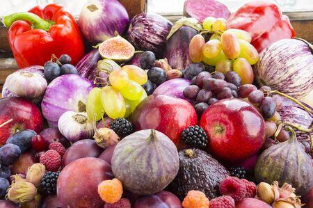 Background of fresh vegetables and fruits. Purple eggplant, plums, figs, apples, raspberries, avocado, grape, hazelnut, sweet pepper, tomato and garlic.Immunity system improvement. Antiviral treatment Imagens