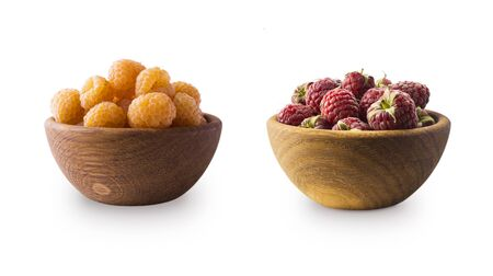 Raspberries in wooden bowl. Yellow and red raspberries isolated on white. Delicious yellow raspberry with copy space for text. Immunity system improvement. Antiviral treatment. Coronavirus prevention.