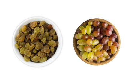Grapes and raisins Kishmish isolated on white background. Top view. Grapes and dried fruit in a wooden bowl isolated on white background. Top view. Green grapes Kishmish with copy space for text.