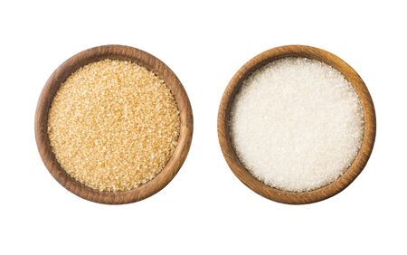 Heap of cane sugar and white sugar isolated on white background. Top view. Heap of brown and white sugar on white background. Wooden bowl of dark sugar isolated on white background. Selective focus.
