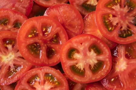 Red tomatoes background. Top view. Healthy natural food, background. Tomatoes slices. Group of ripe tomatoes forming a background. Immunity system improvement. Coronavirus prevention.