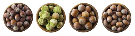 Hazelnuts in a wooden bowl isolated on white background, top view. Shelled hazelnuts in a bowls. Copy space for text. Set of hazelnuts.
