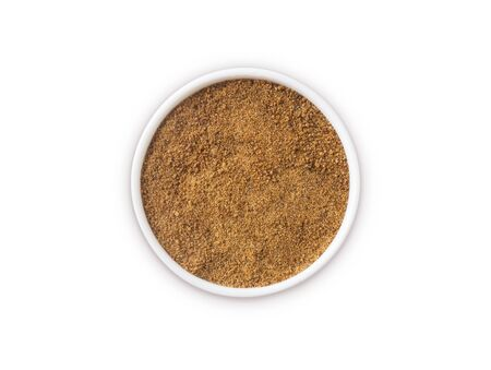 Heap of coconut sugar isolated on white background. Top view. Heap of coconut sugar on white. Dark sugar isolated on white. Organic coconut unrefined sugar, isolated. Selective focus.