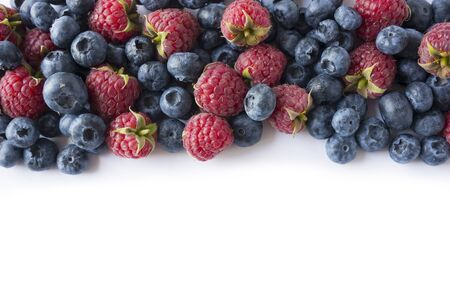 Berries on white background. Ripe blueberries and raspberries. Background of mix berries with copy space for text. Pink and blue food on white background.  Imagens