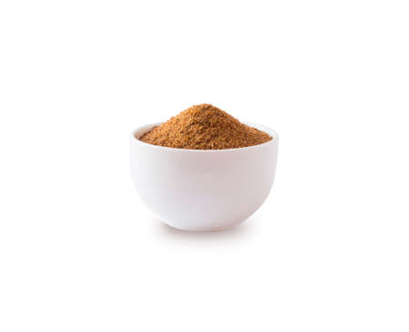 Heap of coconut sugar isolated on white background. Heap of coconut sugar on white. Dark sugar isolated on white. Organic coconut unrefined sugar, isolated. Selective focus.