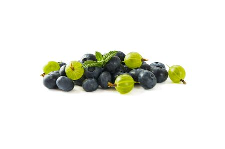 Berry isolation. Green and blue berries isolated on white background. Gooseberry and blueberry with copy space for text. Mixed berries isolated on white. Heap of berries on white background.