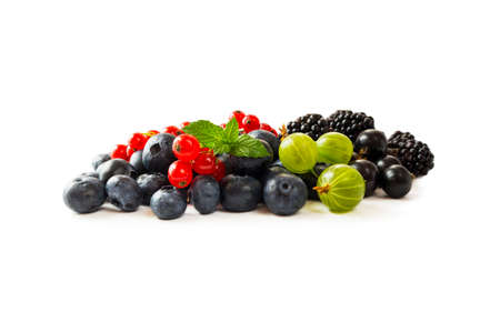 Berry isolation.Mix berries isolated on white background. Blueberry, currant, gooseberry and blackberry with copy space for text. Mixed berries isolated on white. Heap of berries on white background.