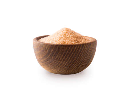 Heap of cane sugar isolated on white background. Heap of brown sugar on white background. Wooden bowl of dark sugar isolated on white background. Sugar in wooden bowl for cooking, isolated. Selective focus.