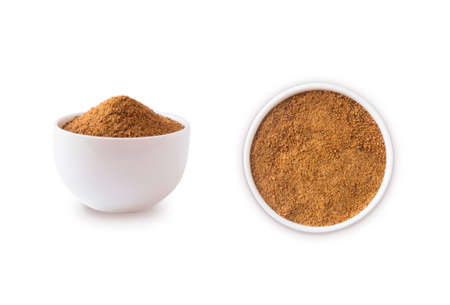 Heap of coconut sugar isolated on white background. Heap of coconut sugar on white. Dark sugar isolated on white. Organic coconut unrefined sugar, isolated. Selective focus. Top view.