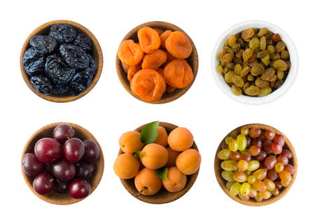 Raisins, grapes, dried apricots, apricots, dried prune and plums isolated on white background. Collage of fresh fruits, dried fruits. Top view. Dried fruits and fresh fruits with copy space for text. Imagens
