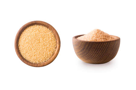 Heap of cane sugar isolated on white background. Heap of brown sugar on white background. Top view. Wooden bowl of dark sugar isolated on white background. Sugar in wooden bowl for cooking, isolated. Selective focus.