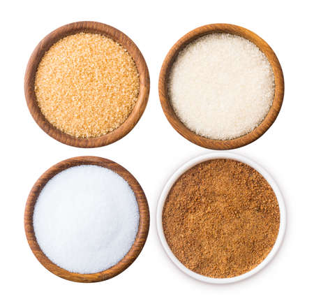 Heap of cane sugar, coconut sugar, white sugar and erythritol isolated on white Top view. Sugar substitute and natural sugar on white background. Wooden bowl of sweetener isolated. Selective focus.