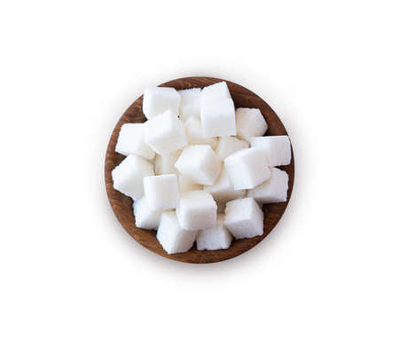 Wooden bowl with white sugar cubes. Sugar cube isolated on white. Selective focus. Sugar cube in wooden bowl on white background. Top view.