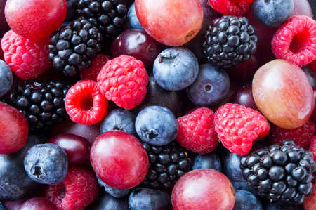 Background of fresh vegetables and fruits. Ripe blackberries, blueberries, plums, pink grapes, raspberries. Mix berries and fruits. Top view. Black-blue and red food. 免版税图像
