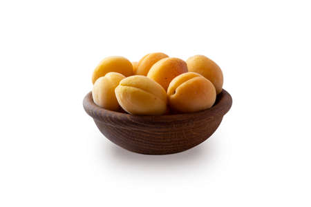 Heap of apricots isolated on white background. Ripe apricots with copy space for text. Apricots in a wooden bowl on white background. Fresh summer fruits.
