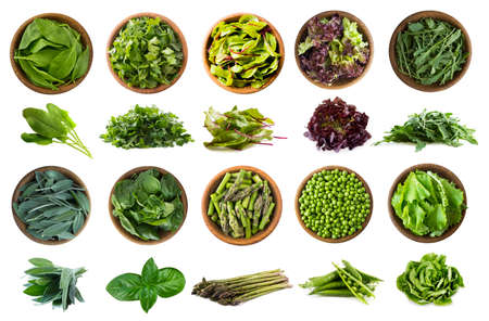 Leafy vegetables isolated on white. Spinach leaves, parsley, mangold, lettuce, arugula, sage, basil, asparagus, green peas, isolation. Vegetables with copy space for text. Top view and other angles.
