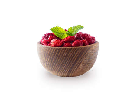 Wild strawberries on white background. Wildberries on a wooden bowl. Ripe wild strawberry isolated on a white background. Strawberries with copy space for text.