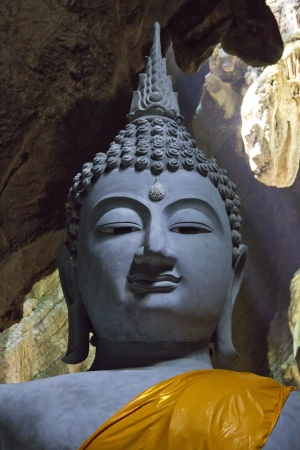 buddha statue inside a mysterious cave in thailand photo