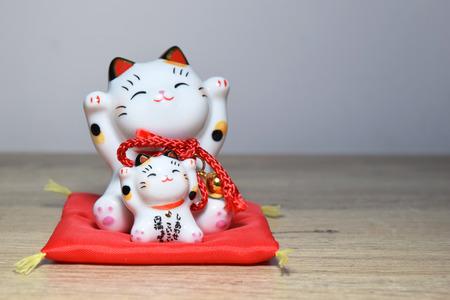 Maneki-neko is a common Japanese figurine (beckoning cat) Stock Photo