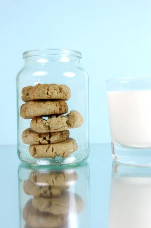 Milk and cookies isolated against a blue background photo