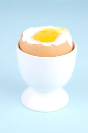 Hard boiled eggs and egg cups isolated against a blue background Stock Photo