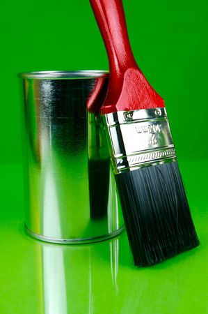 tin: Paints and brushes isolated against a green background
