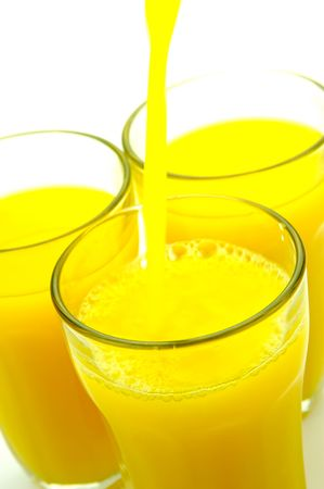 Orange juice being poured into a glass isolated against a white background