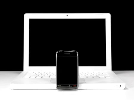 syncing: A mobile phone and a laptop isolated against a black & white background Stock Photo
