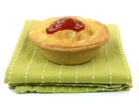 An Australian meat pie served on a napkin isolated against a white background
