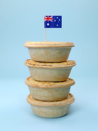 meat pie: A stack of  Australian meat pies isolated against a blue background with an Australian flag
