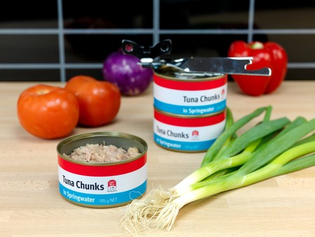 kitchen bench: Cans of Tuna isolated on a wooden kitchen bench