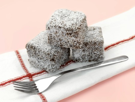 Small lamington cakes isolated against a pink background Stock Photo