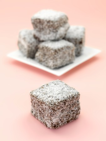 lamington: Small lamington cakes isolated against a pink background Stock Photo