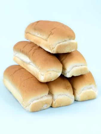 Plain hotdog buns isolated against a blue background photo