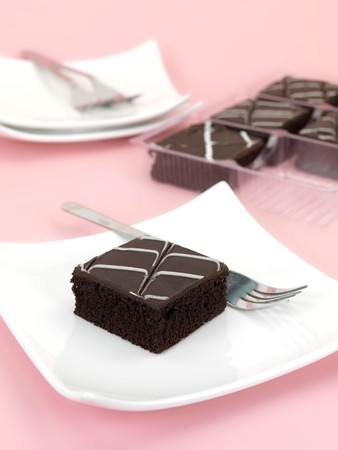 Chocolate mud cake slices isolated against a pink background Stock Photo