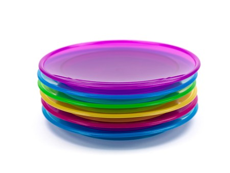 A stack of plastic plates isolated against a white background photo