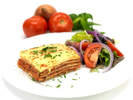 lasagna: Lasagne plated up with a salad and isolated against a white background