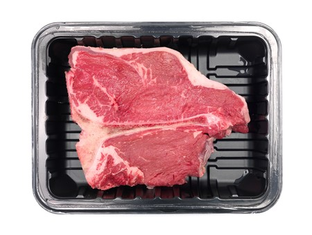 t bone: A T Bone steak in a plastic supermarket tray isolated against a white background