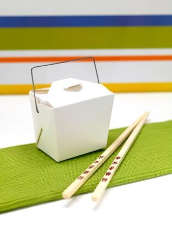Chop sticks and a takeaway box on a kitchen bench photo