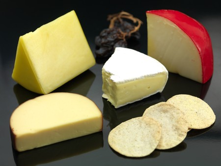 A selection of cheeses a black background