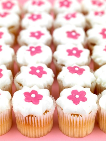 hundreds and thousands: Freshly baked cup cakes with pink flowers and white frosting