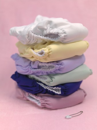 A stack of modern cloth nappies isolated against a pink background Stock Photo - 7513616