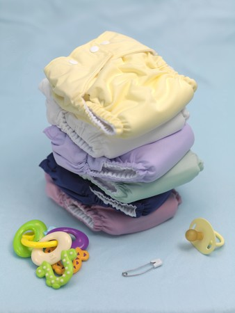 A stack of modern cloth nappies isolated against a blue background Stock Photo - 7513619