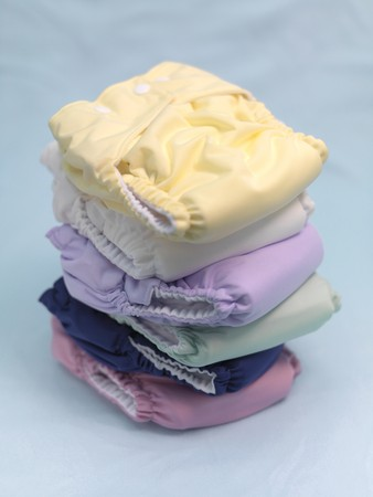 nappies: A stack of modern cloth nappies isolated against a blue background Stock Photo